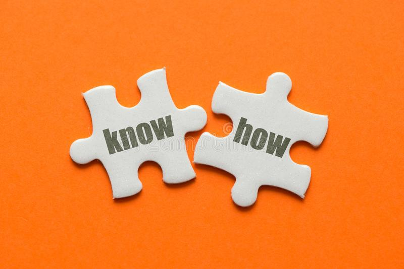 Two white details of puzzle with text know how on orange background, close up.  royalty free stock photography