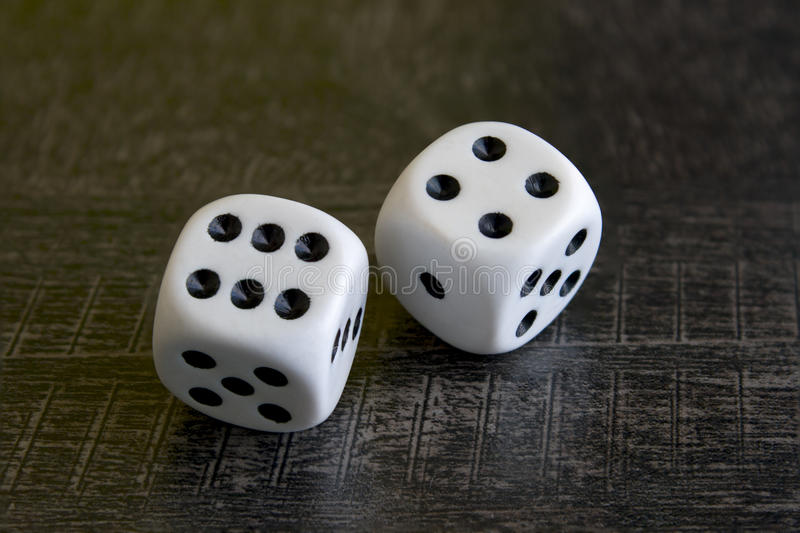 Two white dice gamble on a black background royalty free stock photography