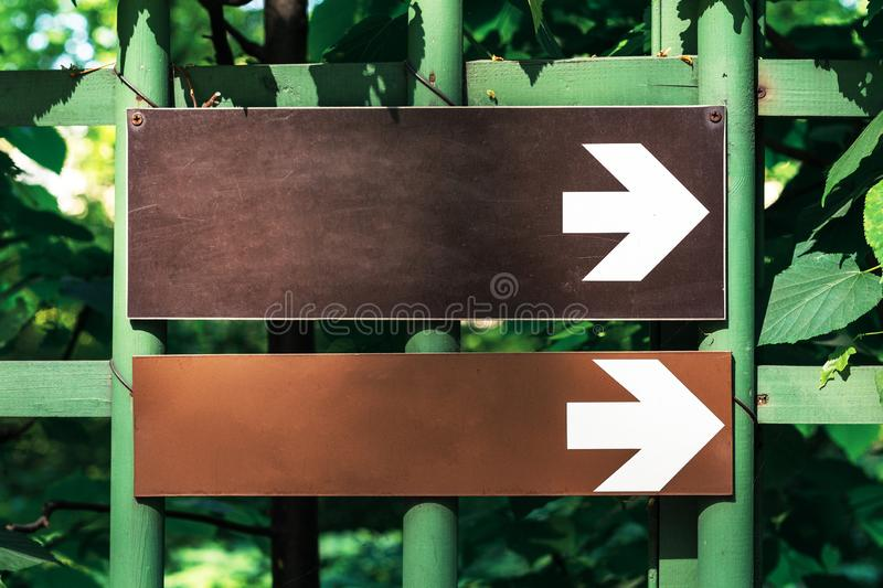 Two white directional arrow road sign point to the right in the park against the background of green trees stock images