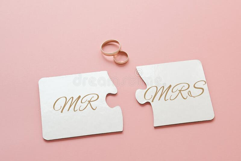 Two white disconnected puzzles with the inscription Mr. and Mrs. and two gold wedding rings on a pink. Background royalty free stock photo