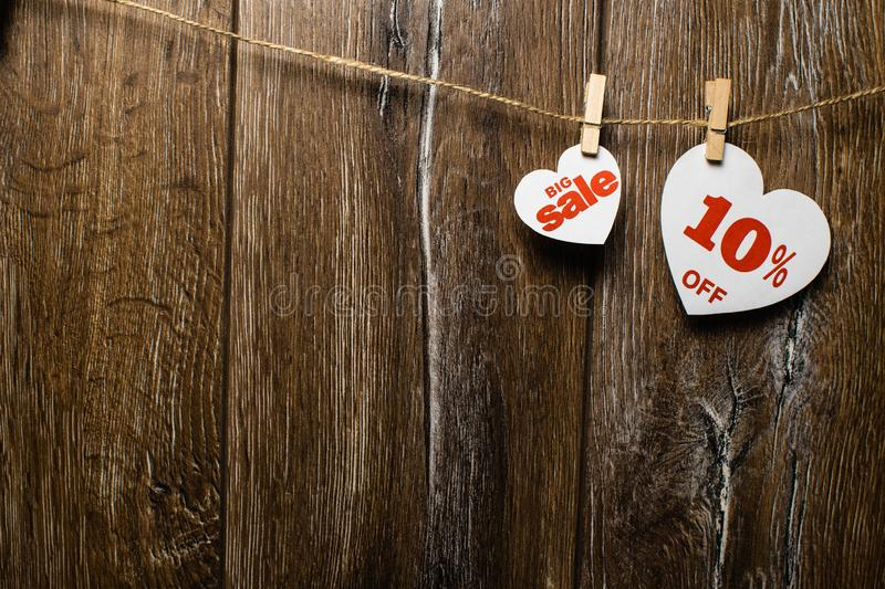Two white hearts and discounts with romantic pattern on wooden background. Big sale in one heart. And ten percent on another hanging on rope by clothespins royalty free stock image