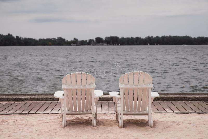 Two White Lounge Chairs Beside Body of Water royalty free stock photo
