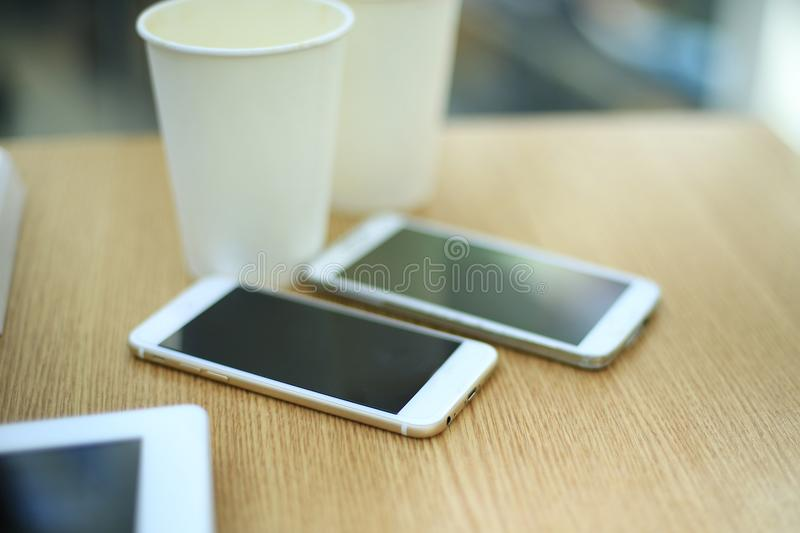 Two white mobile phones with tablet on wooden table background, blank screen electronic device with copy space. royalty free stock photo
