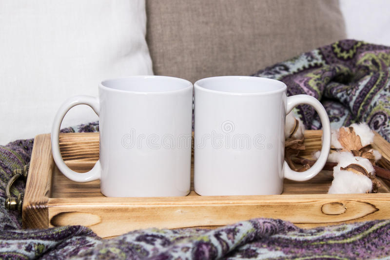 Two white mugs, pair of cups on a wooden tray, the Mockup. Cozy home, wooden background, cotton and wool decorations, winter gifts royalty free stock images