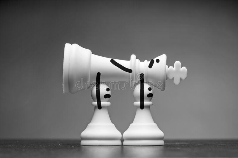 Two white pawns carrying away a king chess piece royalty free stock photo