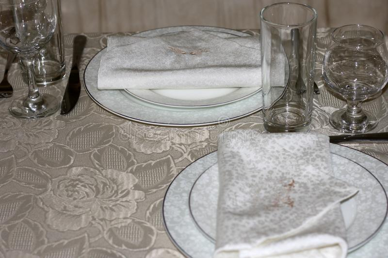 Two white plates with napkins, wine glasses, forks and knives on a table covered with a silk tablecloth. Table setting royalty free stock images