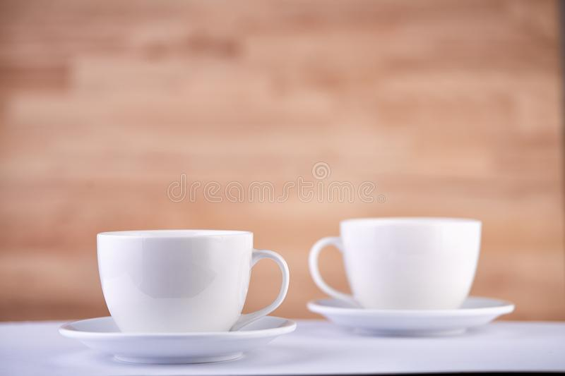 Two white porcelain teacups on wood texture surface show clean and simple design ideas. Selective focus. Two white porcelain tea or coffee cups arranged together royalty free stock photos