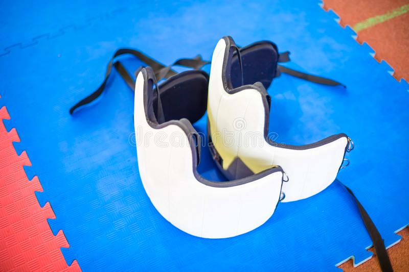 Two white protective vest fo martial arts on a blue floor. Karate protection equipment stock image
