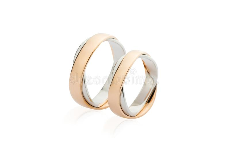 Two white and rose gold wedding rings isolated on white background stock photos