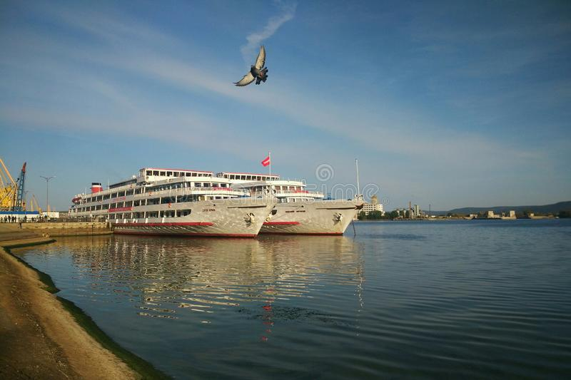 Two white ships at the pier in Togliatti. Two white ships on the pier in Tolyatti and a flying dove royalty free stock photos