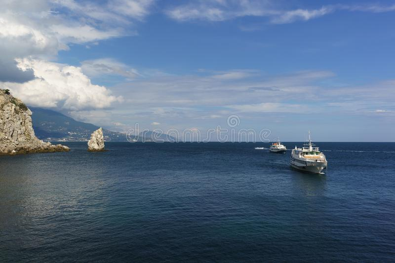 Two white ships sail the calm blue sea on a Sunny day. Cape Limen-Burun and rock Sail in the black sea resort of Crimea stock photos