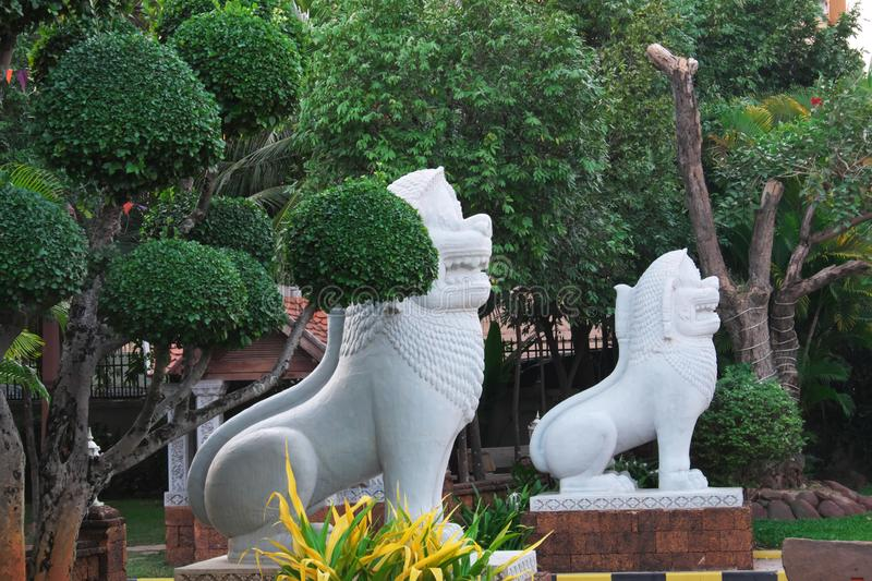 Two white stone sculptures of lions near beautifully trimmed ornamental trees.  royalty free stock images