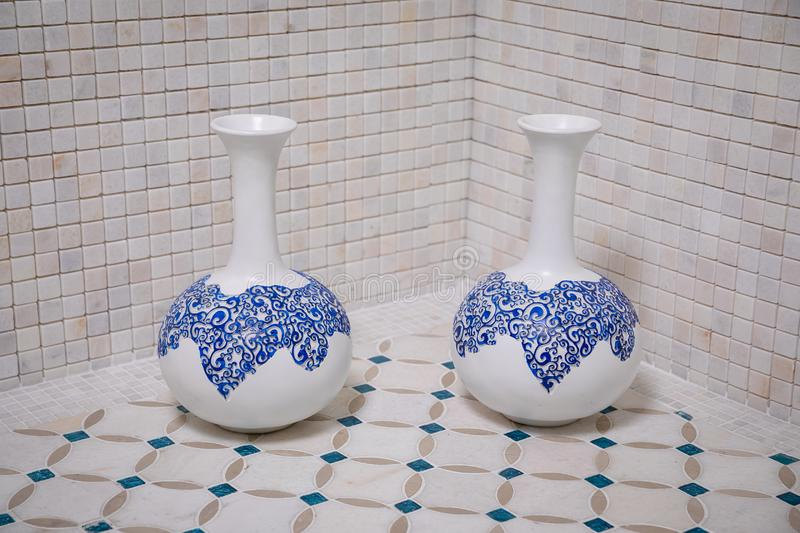 Two white vases with blue patterns standing on a beige broom with blue lines on the background of a wall of beige marble tiles in. The form of squares stock images