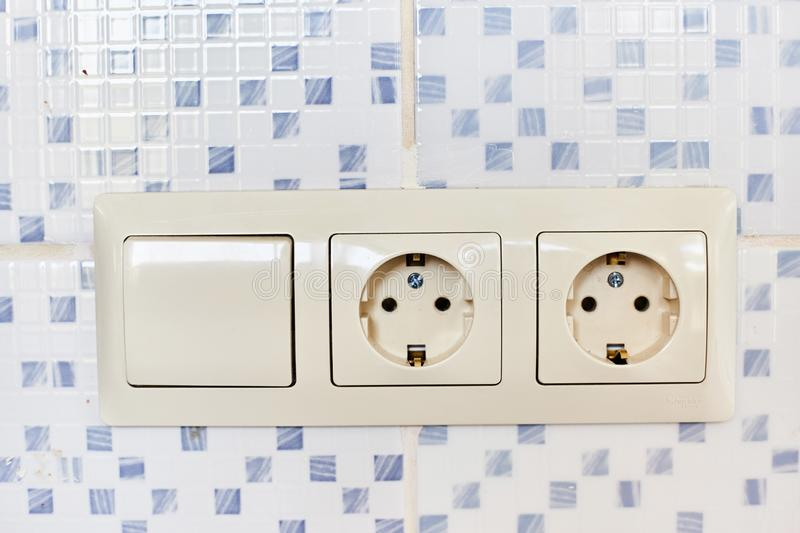 Two white 220-volt outlets with a switch.  royalty free stock photos