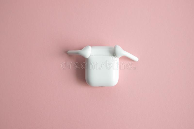 Two white wireless earphones lying on the sides of the closed charger. Pink background. Place for text stock images