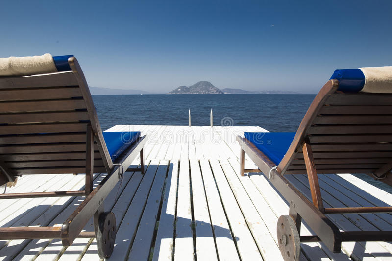 Two white wooden beach couches on a plank pier near the blue sea stock photos
