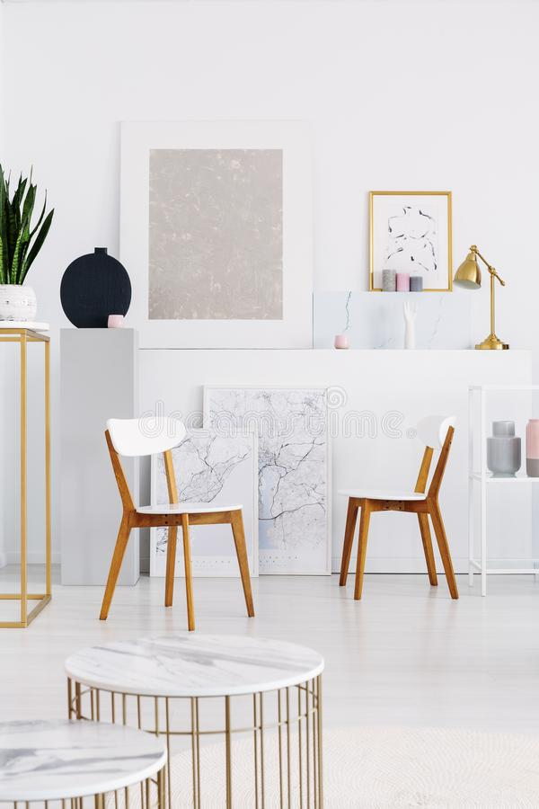 Two white wooden chairs, and tables with marble counter tops in white living room with maps and and art stock photos
