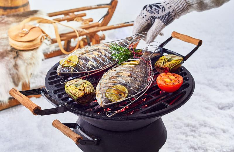 Two whole fish grilling over a winter barbecue. Outdoors in fresh white snow with a gloved hand turning them over the coals stock photos