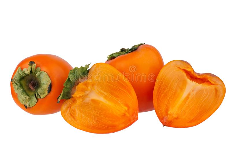 Two orange persimmons fruits or diospyros kaki and two halves of one persimmon on white background isolated close up. Two whole orange persimmons fruits or royalty free stock image