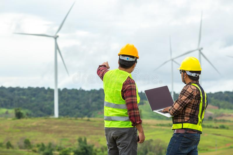 Two Windmill engineer inspection and progress check wind turbine at construction site royalty free stock photo