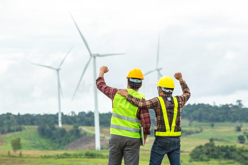 Two Windmill engineer inspection and progress check wind turbine at construction site And succeeded in the mission stock images