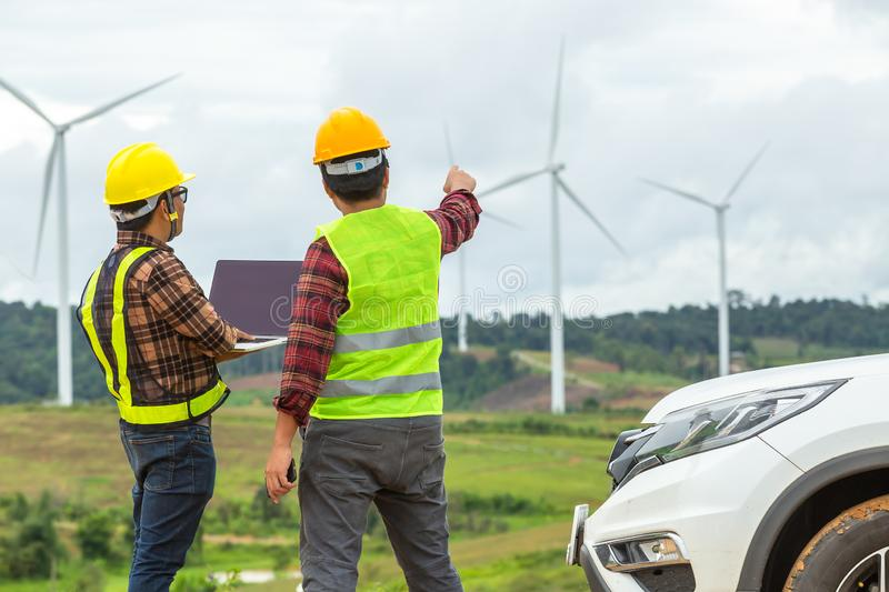 Two Windmill engineer inspection and progress check wind turbine at construction site By using a car as a vehicle stock image