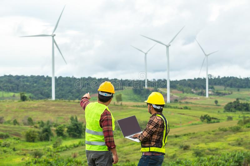 Two Windmill engineer inspection and progress check wind turbine at construction site By using a car as a vehicle royalty free stock image
