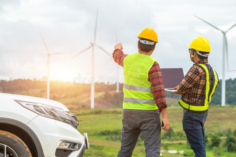 Two Windmill engineer inspection and progress check wind turbine at construction site By using a car as a vehicle stock photo