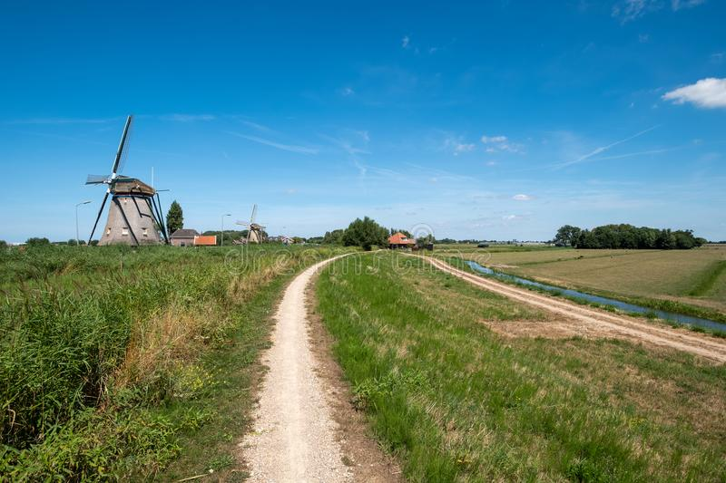 Two windmills on a along the polder near Maasland, the Neth royalty free stock photography