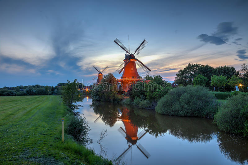 Two windmills in Greetsiel at the blue hour. Germany stock photo