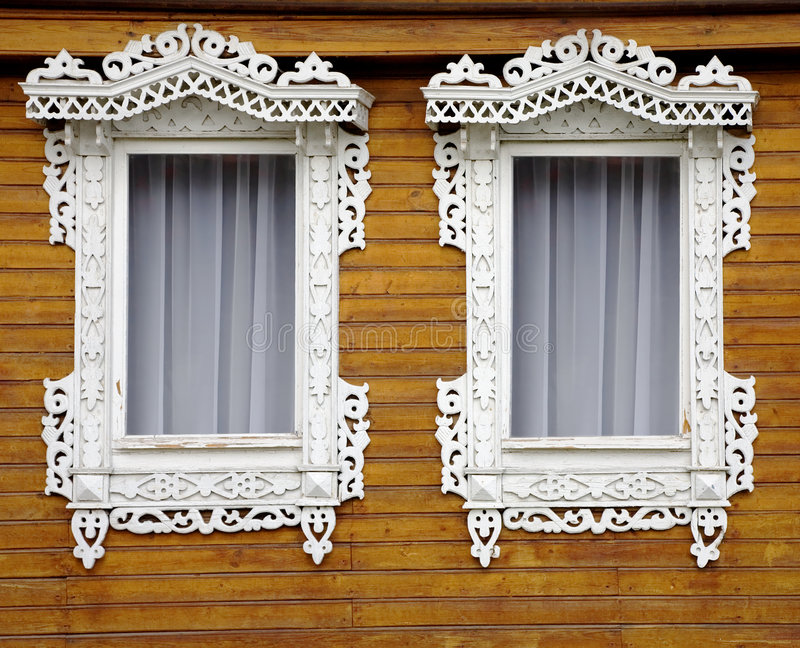 Two windows. From old wooden yellow wall royalty free stock photography