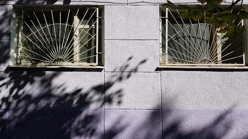 Two windows protected by white gratings and light blue violet rough wall stock images