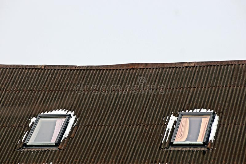Two windows in the snow on a slate roof against the sky stock image