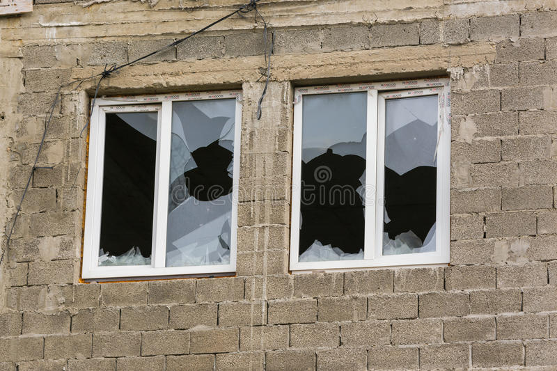 Two windows in an unfinished house with broken windows royalty free stock photography