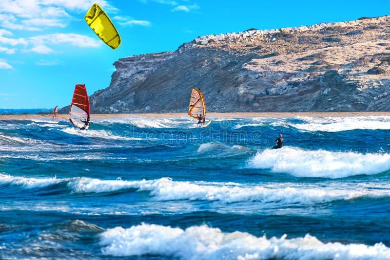 Two windsurfers and kiteboarder ride on Prasonisi beach Rhodes, Greece royalty free stock photo