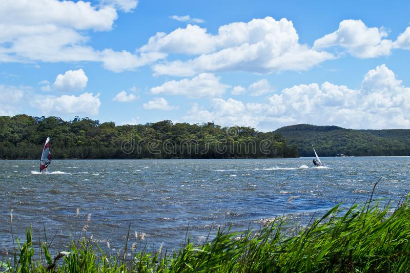 Two windsurfers struggling with a strong wind. On Narrabeen Lagoon in Sydney stock photo