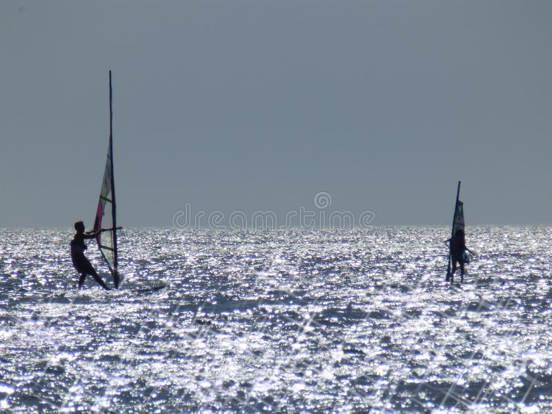 Windsurfers. Two windsurfers on a sunny day royalty free stock photography