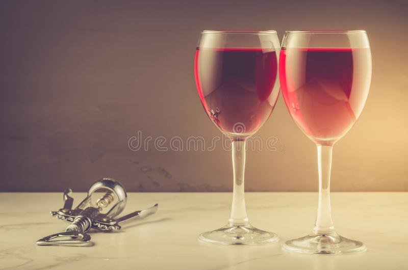 Two Wine glass and corkscrew on a dark background/Two red Wine glass and corkscrew on a dark background. copyspace stock image