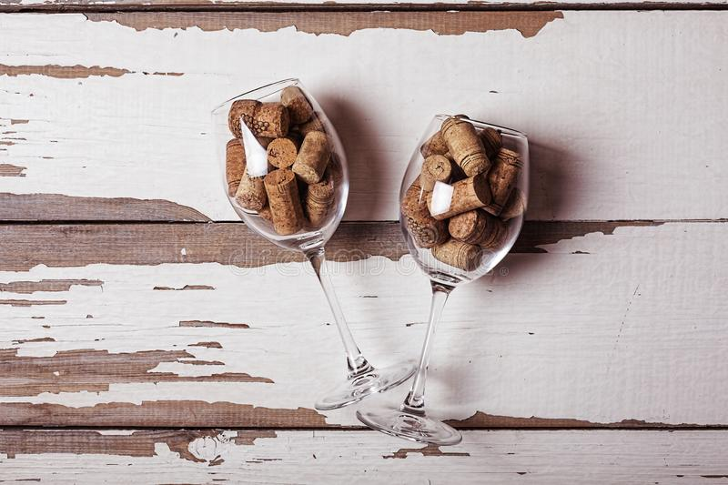 Two, wine glasses, filled, corks, wine bottles, wooden background. Two wine glasses filled with corks from wine bottles on a wooden background. Concept stock photo