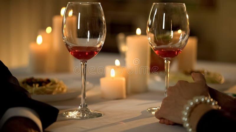 Two wine glasses on holiday table, senior romantic couple celebrating holiday royalty free stock image