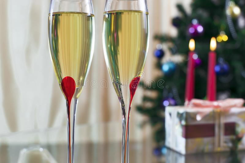 Two wineglass with champagne, Christmas spruce, gifts and candle stock photos
