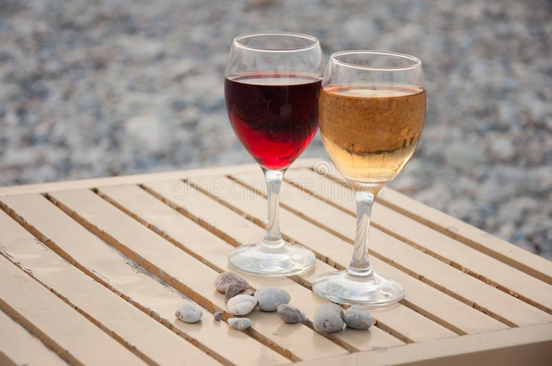 Two wineglass with red, white wine stand on table near in afternoon. Two wineglass with red, white wine stand on beige, table near small grey sea stones in royalty free stock images