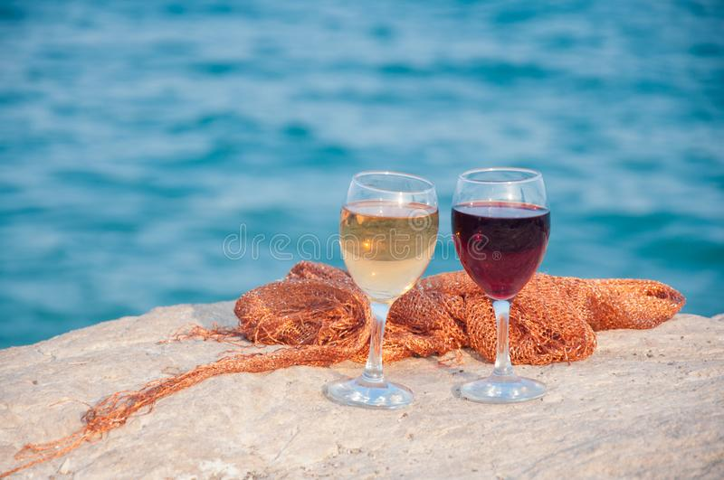 Two wineglass stand on stone in sunny afternoon on blue sea background. Two wineglass with red, white wine stand on stone in sunny afternoon on blue sea stock images