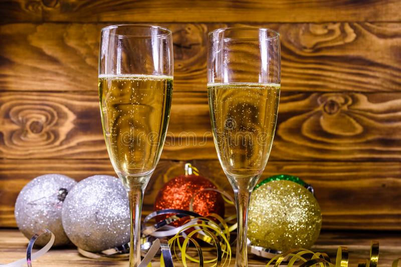 Two wineglasses with champagne and different christmas decorations on wooden table stock photography