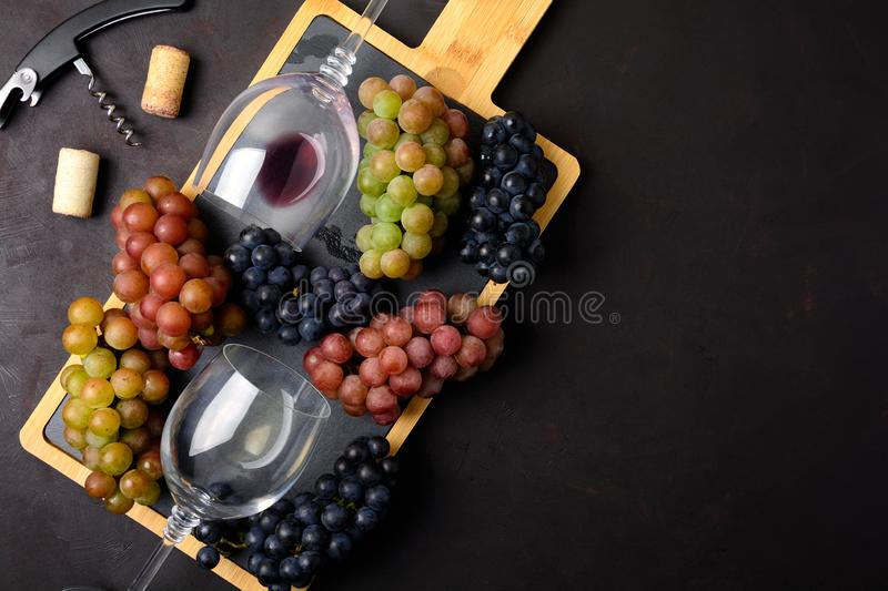 Two wineglasses with red and white wine, grapes, corkscrew and corks lying on dark wooden background royalty free stock photos