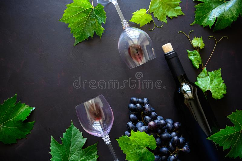 Two wineglasses with red wine, bottle and grape leaves lying on dark wooden background. Top view. Flat lay. Copy space stock images