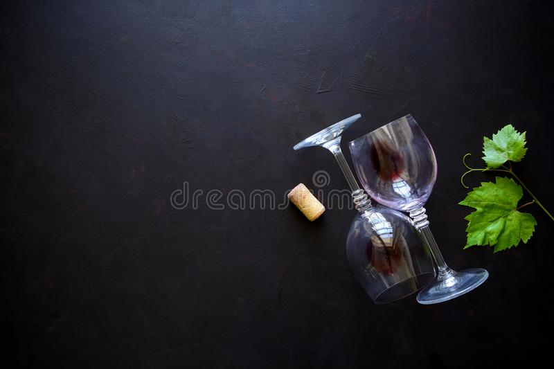 Two wineglasses with red wine, cork and grape leaves lying on dark wooden background. Top view. Flat lay. Copy space royalty free stock photography