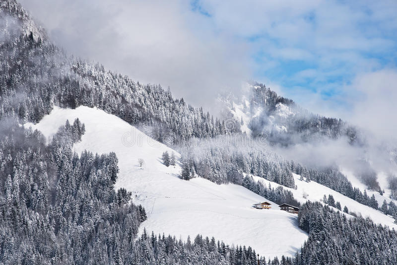 Two winter chalets by the mountain. Typical austrian winter season landscape with chalets by the mountain royalty free stock images