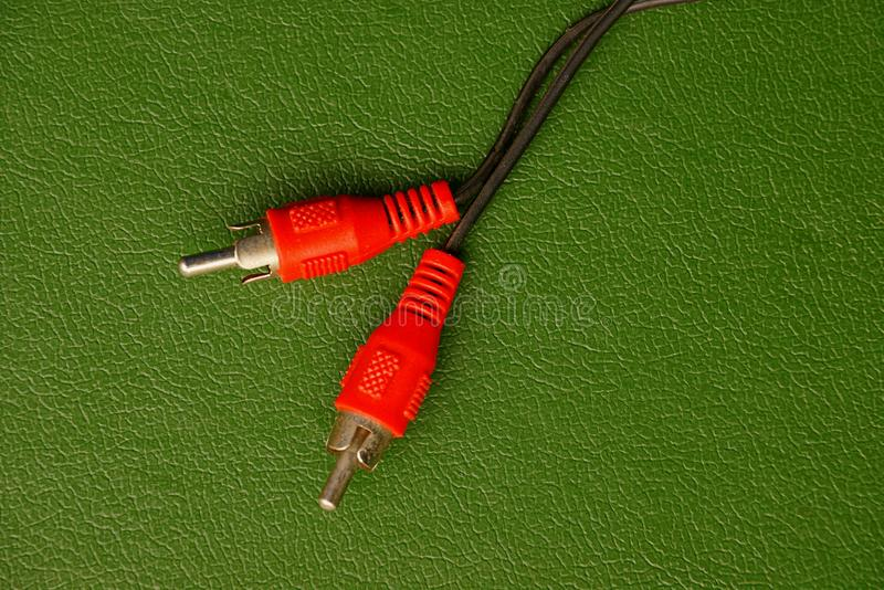 The two wires from the plug on the green background royalty free stock images