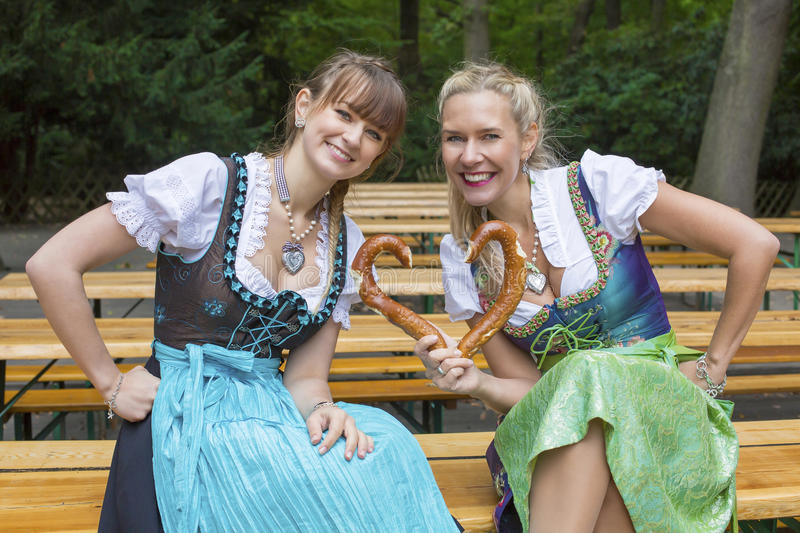 Two woman in dirndl with pretzel stock photo